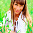 Portrait of a beautiful woman on a green meadow with hands up — Stock Photo