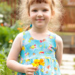 Cute little girl with flowers in her hand — Stok Fotoğraf #3474744