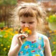 Cute little girl with the flowers in her hand — Stock Photo