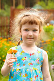 Söt liten flicka med blommor i handen — Stockfoto