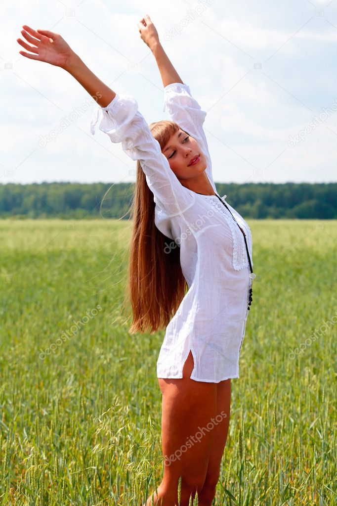 Portrait of a beautiful woman on a green meadow with hands up  Stock Photo #3471743