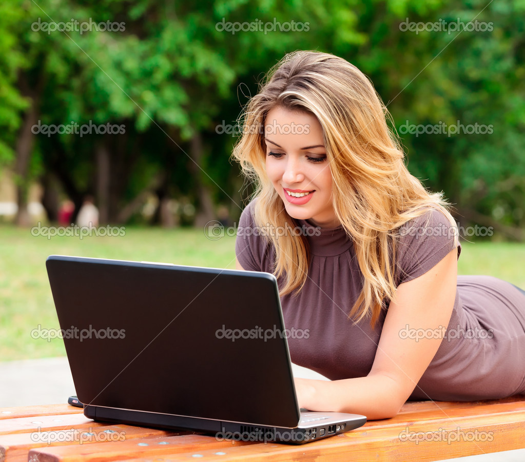 Young pretty woman with laptop lying on the bench in a park — Stok fotoğraf #3493056