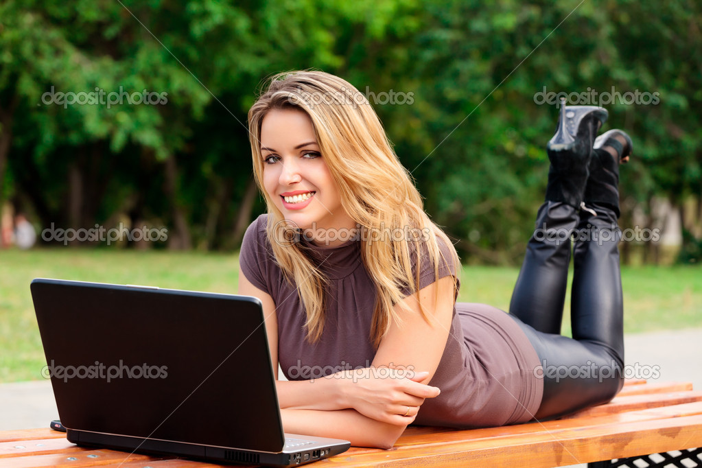 Young pretty woman with laptop lying on the bench in a park — Photo #3493803