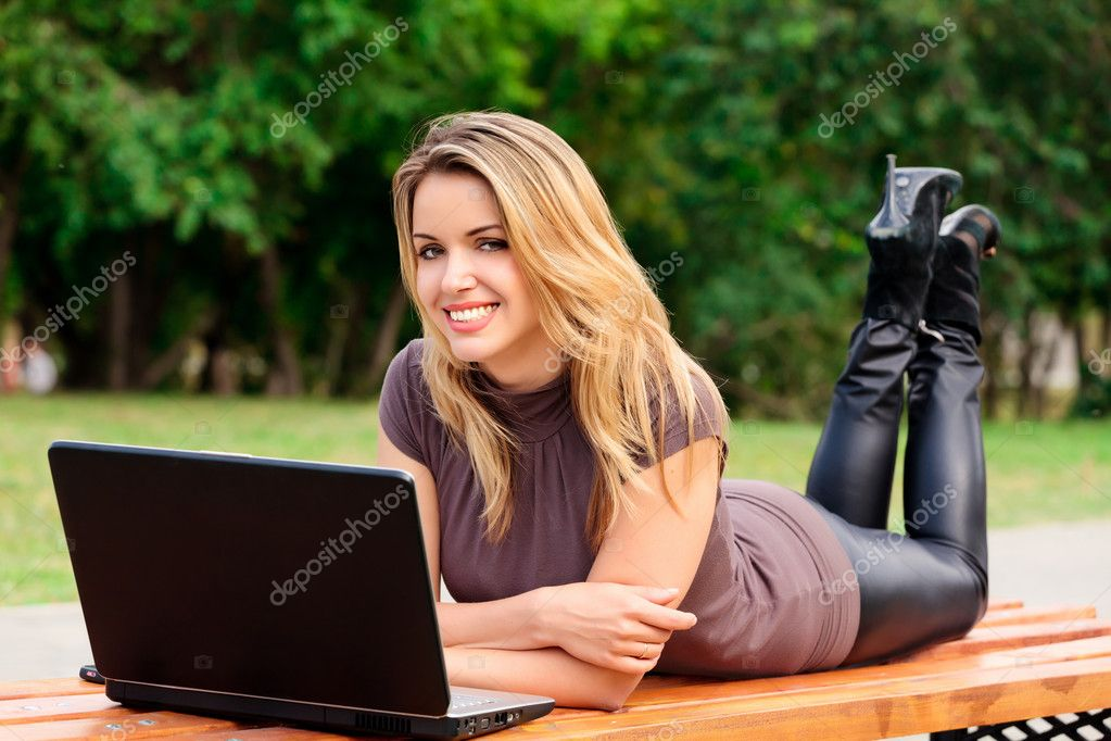 Young pretty woman with laptop lying on the bench in a park — Zdjęcie stockowe #3493803