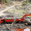 Dump Truck and Excavator in a Quarry - Stock Photo