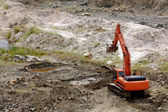 Excavator standing in sandpit with risen bucket — Stock Photo