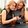 Two smiling girls watching something in mobile phone — Stock Photo #3686862