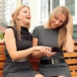 Two smiling girls watching something in mobile phone — Foto de Stock