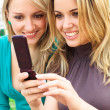 Two smiling girls watching something in mobile phone — Stock Photo #3687144