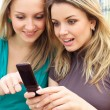 Two smiling girls watching something in mobile phone — Stock Photo #3687244
