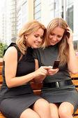 Two smiling girls watching something in mobile phone — Stock fotografie