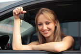 The happy woman showing the key of her new car — Stockfoto