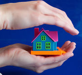 Toy house in human hands - a protection — Stock Photo