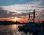 Boats and yachts in the harbor at sunset — Stock Photo