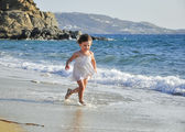 Child running through the waves — Stock Photo