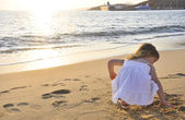 Little girl playing at sunset sea — Stock Photo