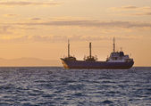 Sunrise at sea and the fishing vessel — Stock Photo