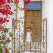 Child near old door with flowers — Stock Photo