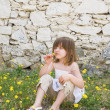 A little girl sitting on the ground — Stock Photo