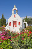 Greek church surrounded by flowers — Stock Photo