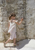 A little girl standing to the wall — Stock Photo