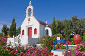 The Greek church is with flowers — Stock Photo