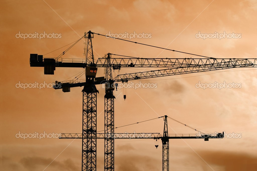 Tower crane silhouettes at a construction site — Stock Photo #3681748