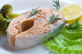 Salmon steak decorated with vegetables — Stock Photo