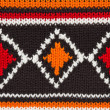 Knit sweater  texture. orange, black and white threads. ornament — Stock fotografie
