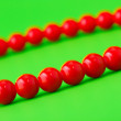 Red beads on green — Stock Photo