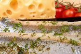Herring on black plate with piece of cheese and tomato cherry — Stock Photo