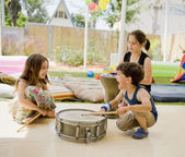 Three kids having fun with drums — Stock Photo