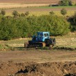 Blue skidder working on field, agro landscape — Stock Photo