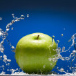 Green apple with water splash on blue background — Stockfoto
