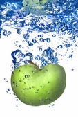 Green apple dropped into water — Stock Photo