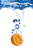 Fresh orange dropped into water — Stockfoto