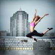 Girl jumping on the roof against city — Stock Photo #3020541