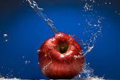 Red apple with water splash on blue — Stock Photo