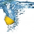 Fresh lemon dropped into water with bubb — Stock Photo