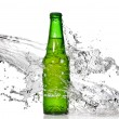 Green beer bottle with water splash — Stock Photo
