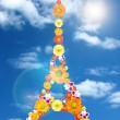 Eiffel tower from flowers with reflection and sun against blue sky — Stock Photo #3378983