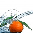 Tangerine with green leaves and water splash  — Stock Photo