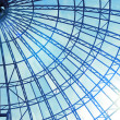 Modern glass roof with blue sky and sun - Stock Photo