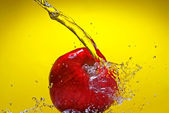 Red apple with water splash on yellow background — Stock Photo