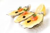 Oysters with sauce and lemon — Stock Photo