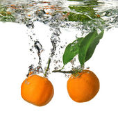 Tangerine dropped into water with bubbles — Stock Photo