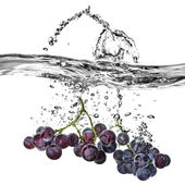 Blue grape dropped into water with splash — Stock Photo