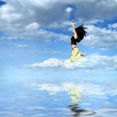 Ragazza saltando contro sole e cielo blu — Foto Stock