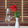 Wineglass and rose on the table — Stock Photo