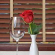 Wineglass and rose on the table - Lizenzfreies Foto